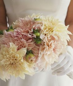 "Bride holding bouquet of dahlias | You've given an enthusiastic ""yes!"" to the proposal, but there's still a lot to sort out before you say ""I do."" Use this step-by-step guide to create a wedding binder that will keep you organized (and sane) throughout the planning process."