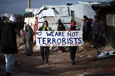Migrants carry a placard as part of the 'jungle' migrant camp is cleared on February 29 2016 in Calais France The French authorities have begun...
