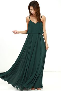 We're absolutely love struck over the Love Runs High Forest Green Maxi Dress! Forest green woven poly falls from adjustable straps into a tiered, triangle bodice above a cascading maxi skirt full of volume. Hidden side zipper.