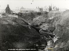 Postcard photograph entitled The Dene From North Road, Seaham Harbour. 32809 J.V., showing a gorge with steep wooded sides and a stream at the bottom; a fence is running down the slope on the left of the picture; in the distance on the top of the cliff, a church, rows of terraced houses, and a large imposing house can be seen
