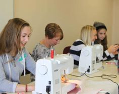 Young girls learn to sew in groups around their sewing machines during a sewing workshop in South East. Find your way back into sewing with Cotton Club
