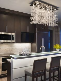 Lower Level Gally kitchen design with bubble chandelier with custom cabinetry and glass lit bar Tutto Interior Design Project Portfolio | Tutto Interior Design Michigan