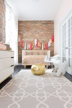 Modernize a nursery room with brick walls, and warm it up with some fun tassel garland