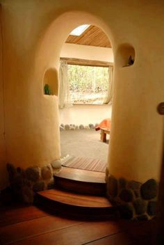A cool arched doorway into a raised living area. Many possibilities with cob and other natural building methods!  This Cob House