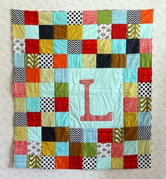 Initial Patchwork Baby Quilt    I like this idea better than the whole applique name ... maybe stitch the name in cursive with dark DMC floss ... below the initial?  Work on developing this idea ..