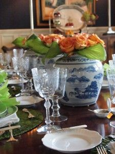 Nice but non-traditional setting for fall--Mary Carol Garrity uses three ginger jars filled with orange roses to go with her blue transferware and white plates.  Love it.