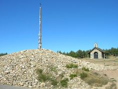 Pilgrims leave a rock from their home town on the base of the Cruz de Ferro cross on the Camino de Santiago trail