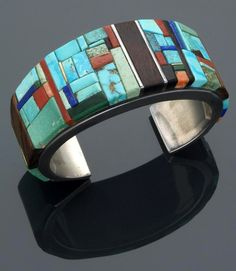 Cuff | Charles Loloma (Hopi Pueblo).  Silver set with a mosaic of turquoise, lapis lazuli, coral, ironwood, silver and gold, the bottom tips undecorated.