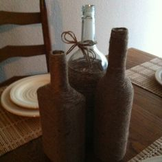 Empty liquor bottles wrapped in jute twine. Used hot glue to start the bottom wrap around and also toward the top when the bottle curves inward. I plan to get some pretty fake flowers to put in them :)