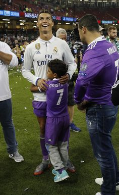 Real Madrid's Portuguese striker Cristiano Ronaldo is hugged by his son Cristiano Ronaldo Jr. after Real Madrid won the UEFA Champions League final football match between Juventus and Real Madrid at The Principality Stadium in Cardiff, south Wales, on June 3, 2017. / AFP PHOTO / Adrian DENNIS
