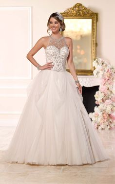 Victorian-inspired dress from Stella York is made of luxurious tulle satin, features a beaded illusion halter with hand-sewn Diamantes and a double keyhole back.