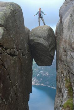"""Kjeragbolten is a boulder wedged in a mountain crevice in the Kjerag mountains in Norway. Below the boulder is a sheer drop of about 3200 feet (1000 meters) to Lysefjorden."""