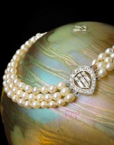 Cartier - An Art Deco cultured pearl and diamond necklace, French, circa 1920. Designed as three rows of fifty-six, fifty-eight and fifty-six cultured pearls, measuring approximately 5.3 x 4.3 to 4.3 x 3.9mm., centering a pear-shaped openwork panel of baguette and old European-cut diamonds, completed by a rose-cut diamond two-row clasp; signed Cartier Paris; mounted in platinum; length: 12 3/4in.