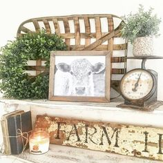 Farmhouse vignette: old scale, chippy sign, old books tied together with twine, greenery, tabacco basket
