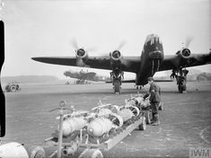 Armourers wait for the conclusion of an engine test on Short Stirling Mark I, 'OJ-N', of No. 149 Squadron RAF, parked at the end of the south-east runway at Mildenhall, Suffolk, before loading her with 250 lb GP bombs for a night raid on Essen, Germany. Each bomb has been fitted with a shackle to enable it to be winched into position in the Stirling's high bomb-bay. [Photo by Brock, F. J. (Flying Officer). © IWM (CH 5135).]