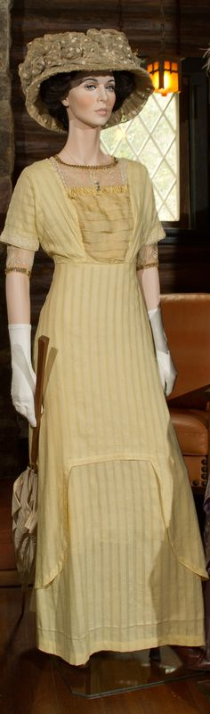 Day Dress: Pale yellow ribbed silk with china silk front, c. 1911. Mushroom Hat: Cream cotton netting poufs over hat wire frame, c. 1911. Parasol: White embroidered cotton with oak handle, c. 1911.