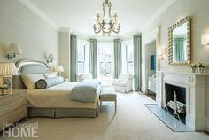 The master bedroom features floor-to-ceiling windows (flanked by Indian shutters and blue-and-gold silk drapes) that look out onto Commonwealth Avenue. A buttercream-colored rug keeps things light. A television and dresser are neatly tucked away in one of the room's two alcoves.