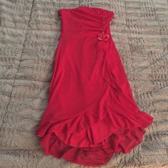 Lovely red dress Beautiful strapless dress in rich red color with subtle silver sparkle pattern and slight high-low, knee length hem. Gentle gathering on left with flower embellishment. Great for Valentine's Day or holiday party. Tag says small but fits more like XS. Dresses Strapless