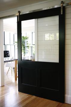 Sliding black barn door with glass panel.