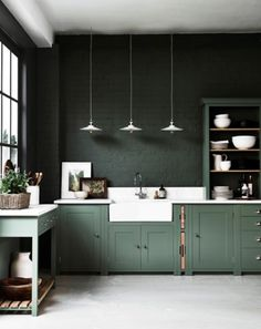 Rich green, brick walls and light green cabinets in a kitchen.
