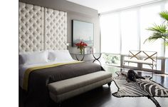 Modern bedroom. Wall mounted tufted headboard white. Grey white yellow color scheme. Bed. Floor to ceiling windows with shades. Zebra rug.  http://cococozy.com