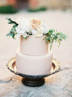 sweet two tier wedding cake with floral topper. love the simplicity!