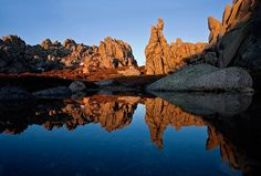Una pequeña laguna de fusión de nieve refleja las formas de las rocas de la Pedriza