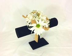 Wrist corsage of white daisies with a burlap ribbon.