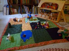 Waldorf Knitted Farm Play Mat. Like how the cable knit field has perfect furrows for planting seeds.