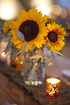 Sunflower centerpieces along a rustic tablerunner.