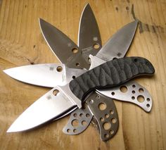 A pile of Spyderco Mule Team Knives, the top one has Anso style handle scales from Cuscadi