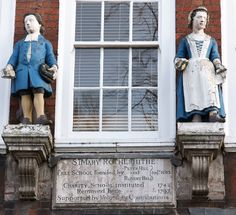 Facing the church of St Mary's Rotherhithe is a charity school built in 1703. Although the teachers and pupils have long gone, two figures still stand on the facade, proudly modelling their uniforms. The figures of schoolgirls and boys placed above the school entrance. They served not only to advertise the educational premises but also to model the school uniform - a real attraction for poor families who could not usually afford such clothes for their children.