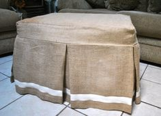 A natural burlap ottoman slipcover with pleats on the center of the sides and corners, and cream color trim on the edge. The burlap is a great way No Sew Slipcover, Ottoman Slipcover, Ottoman Cover, Round Ottoman, Slipcovers For Chairs, Sofa Covers, Adams Furniture, Home Decor Furniture, Furniture Design