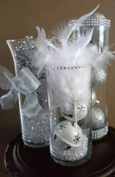 Set of 3 sparkling Winter Wonderland Wedding Reception Centerpieces. You will receive 3 different size vases as described below. Perfect to put all 3 in the center of a table on a circle piece of glass or silver charger plate (neither included). Please feel free to email me with any questions or custom orders you may want! Vase 1 - contemporary glass cylinder vase 10 tall x 3 1/4 diameter. Beautiful Rhinestone mesh at the top and bottom of the vase and 6 sparkling glitter and decorated…