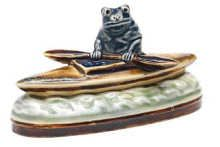 George Tinworth for Doulton Lambeth A model of a frog padling in a canoe, circa 1890 In tones of blue, greens and brown 7cm high, impressed factory mark (R to one paddle). Sold at Bonhams Sep 2008 for £1800