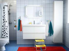 Kupaonica s bijelim pločicama, bijelim GODMORGON umivaonikom i elementom te narančastim tepihom