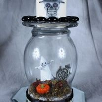 """Ghost are mist in the cemetery in our wine glass centerpiece that comes with a white votive candle or choose our hurricane centerpiece.  Both sit on a 5"""" octagon table mirror. The ground is covered by autumn leaves, pumpkins and black rocks.  Black satin ribbon trims the glass.  Picture and pri..."""