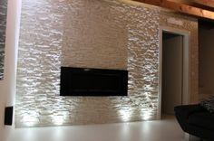 una parete bianca a rilievo illuminata con faretti led che creano bellissimi giochi di luce