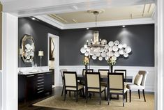 The formal dining room has white wainscoting around the bottom of the room, while the top majority of the wall is painted a dark navy. A collection of elegant china plates of different sizes and shapes are arranged on the wall behind the table as art. A swanky chandelier with tons of hanging crystals hangs from the shallow tray ceiling over the black dining table. A small marble-topped buffet is on the left wall, topped with decanters and two delicate lamps.