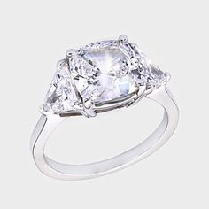 3.5 Ct. Cushion-cut  14K Three Stone Ring. This high quality cubic zirconia ring features a 3.5 carat cushion-cut center with 0.55 carat triangle on each side. An approximate 4.6 total carat weight. This classic cubic zirconia ring is set in solid 14K white gold, and is available in 14K yellow gold via Special Order. Cubic zirconia weights refer to equivalent diamond carat size.