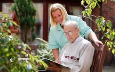 A carer and resident at an outside table