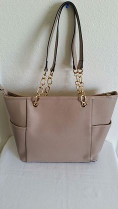 New (never used) - Tan tote with gold accents and divider on the inside. Brand new.