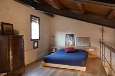 The headboard was made by a carpenter with the remains of the mezzanine wooden floor.