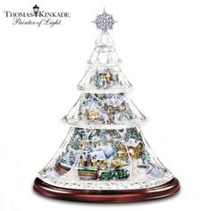 Exclusive! Hand-cut crystal Christmas tree holds a 3D village inside. Plays a medley of Christmas songs, while a miniature train circles the base.