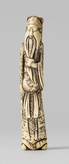 "A long stag antler netsuke of Kan'u. 18th/early 19th century. 	Standing stroking his long beard and holding his halberd named ""Blue Dragon"", the robe engraved with a dragon rising from stylized waves."