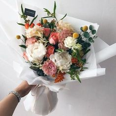 Gorgeous Wedding Bouquet! To me it looks a little fallish, with the soft burnt orange color. I love the peach and soft pinks. We have some roses in there, possibly carnations, but what are those yellow ball thingies on the top section of the flowers?
