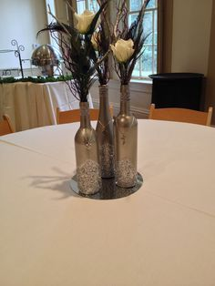 DIY center pieces made from wine bottles! Maybe minus the jewelry, but I like the dark look of it.