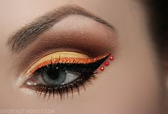 Defined orange glitter eye liner is accented with a trio of crystals.