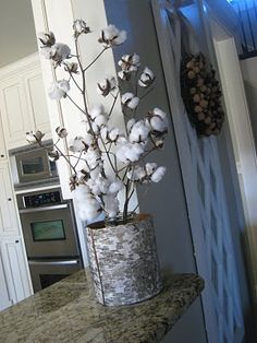 Cotton branches in a glass container covered by a Birch sleeve