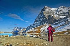 "Standing in front of the Mighty Eiger. (3,970 meter Alt.) Canton of Bern, Switzerland. No. 1481. ""The Eiger is a 3,970-metre (13,020 ft) mountain of the Bernese Alps, overlooking Grindelwald and Lauterbrunnen in the Bernese Oberland, just north of the main watershed and border with Valais. It is the easternmost peak of a ridge crest that extends across the Mönch to the Jungfrau at 4,158 m (13,642 ft), constituting one of the most emblematic sights of the Swiss Alps. While the northern side…"